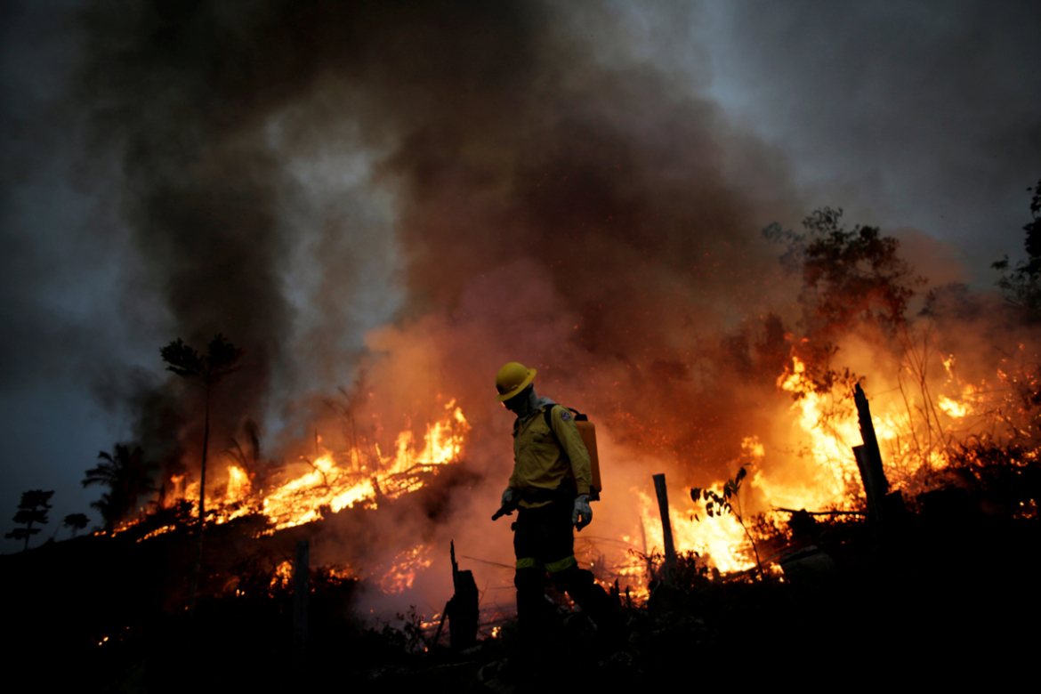 A Brazilian Institute for the Environment and Renewable Natural Resources (IBAMA) fire brigade member attempts to control a fire in a tract of the Amazon jungle in Apui